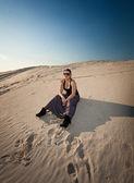 Woman in dress sitting on sand dune — Foto de Stock