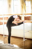 Little ballet dancer stretching in dance class — Stock Photo