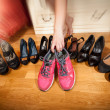 Active woman picking sneakers rather than high heels. Photo with — Stock Photo
