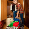 Brunette woman packing clothes in big suitcase — Stock Photo