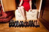 Woman sitting in wardrobe an choosing footwear — Stock Photo