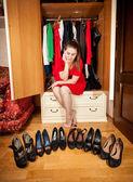 Woman choosing black high heeled shoes at wardrobe — Stock Photo