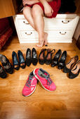 Pink sneakers among black high heeled shoes at wardrobe — Stock Photo