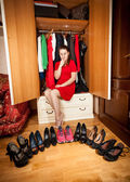 Woman choosing between sneakers and high heeled shoes — Stock Photo