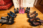 Female hand picking sneakers among high heeled shoes — Stock Photo