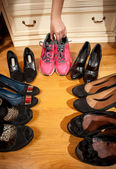 Woman choosing sneakers rather than hugh heeled shoes — Stock Photo
