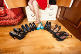 Woman sitting in wardrobe among high heel shoes and ballet flats — Stock Photo