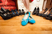 blue ballet flats standing among black high heel shoes — Stock Photo
