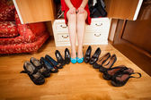 Woman in blue ballet flats sitting between black high heel shoes — Stock Photo