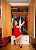 Элегантная женщина, глядя на платья в большой шкаф — Стоковое фото