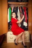 Beautiful woman in red dress sitting at big wardrobe — Stock Photo