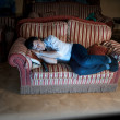 Man sleeping on sofa at night near TV — Stock Photo #45100623