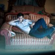 Man lying on sofa and watching TV at night — Stock Photo #45100651