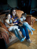 Mother and two daughters watching TV at night — Stock Photo