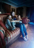Mother with two daughters watching horror movie at night — Foto de Stock