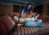 Mother waking up two daughter fell asleep at night while watchin — Stock Photo