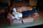 Man switching TV channels on sofa at night — Stock Photo