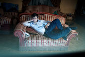Man lying on sofa and watching TV at night — Stock Photo