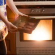 Photo of woman putting cookies in oven — Stock Photo #45316497