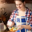 Young housewife preparing salad with cucumbers — Stock Photo #45316729