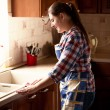 Beautiful woman cleaning kitchen with cloth — Stock Photo #45316959