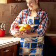 Woman wearing apron holding fresh bowl with fruits — Stock Photo #45317041