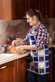 Woman putting grated carrot in bowl — Stock Photo