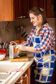 Young woman grating carrot on kitchen — Stock Photo