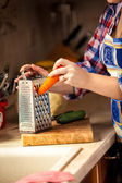 Photo of woman grating carrot on wooden board — Stock Photo