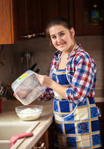 Smiling housewife interspersing flour from bowl — 图库照片
