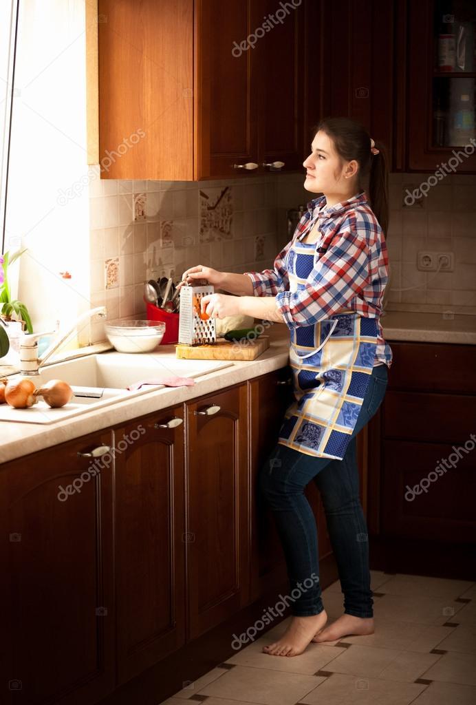 Huisvrouw bezig met klassieke houten keuken met groot raam ...