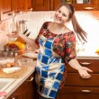 Laughing young housewife in apron on kitchen — Stock Photo