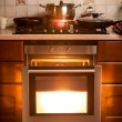 Hot oven and pan boiling on stove at kitchen — Stock Photo #45456489
