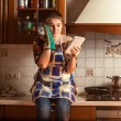 Housewife looking recipe on tablet while sitting on tabletop — Stock Photo #45456587