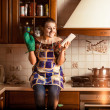 Portrait of housewife sitting on tabletop and using tablet — Stock Photo #45456615