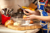 Photo of woman cracking egg with knife — Stock Photo