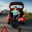 Man sitting on car trunk and holding foot on spare wheel — Stock Photo