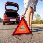 Woman putting warning sign after car crash — Stock Photo #45545563