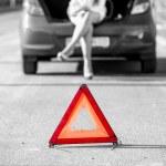 Woman sitting on broken car near red warning sign — Stock Photo