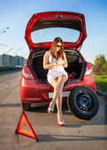 Woman in short dress browsing on tablet how to change wheel — Stock Photo