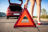 Photo of sexy woman putting warning sign on road — Stock Photo