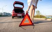 Woman putting warning sign after car crash — Stock Photo