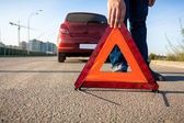 Photo of man putting triangle warning sign on road — Stock Photo