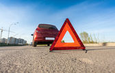 Photo of red triangle sign on road next to broken car — Stock Photo