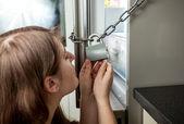 Portret van vrouw op zoek in vergrendelde koelkast — Stockfoto