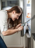 Photo of woman trying to open lock hanging on fridge — Stock Photo