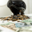 Black piggy bank standing on pile of money — Stock Photo #46217631