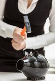 Photo of woman smashing black piggy bank with hammer — Stock Photo