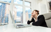 Businesswoman sitting behind table and looking out of window — Stock Photo