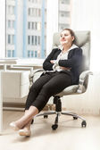 Businesswoman relaxing in leather chair at office — Stok fotoğraf